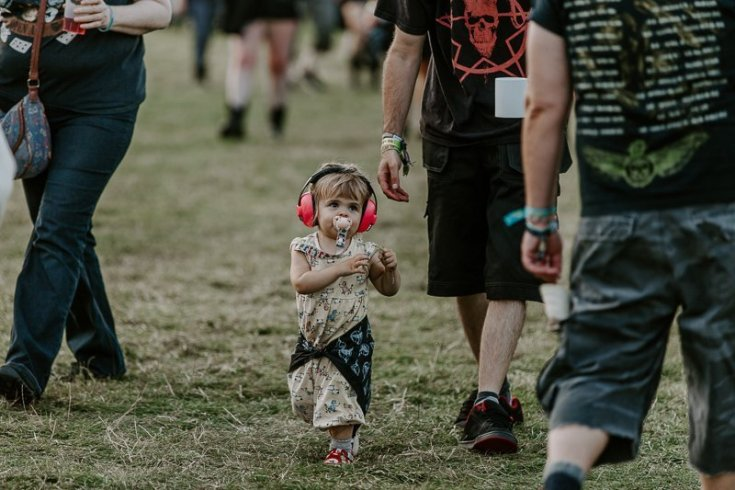 A little girl with a dummy in her mouth and wearing ear defenders at Bloodstock 2019