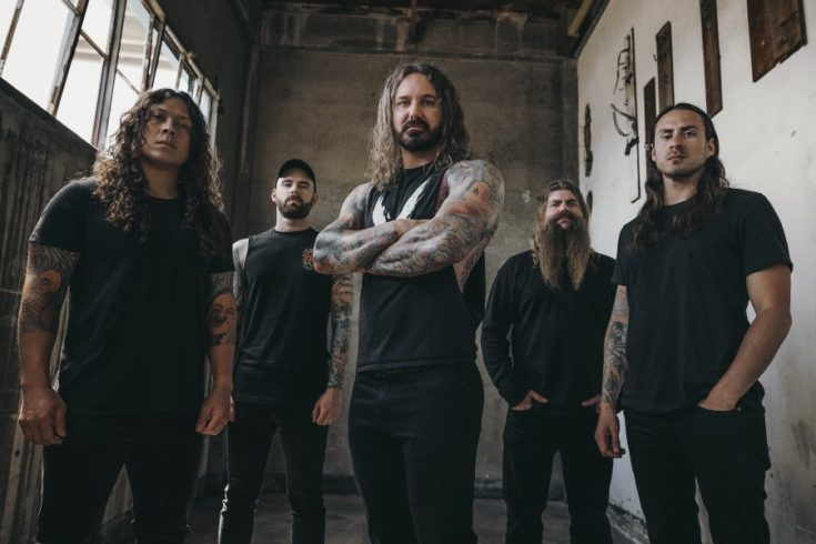As I Lay Dying band photo. The band are stood in what seems to be an old church.