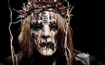 Joey Jordison in a white mask wihich appears to have thick stitches in it, with a crown of thorns on his head