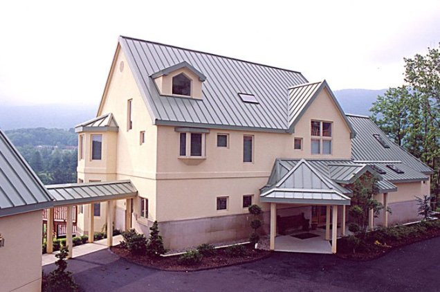 This peachy home features a lovely covered walkway and a dove grey steel sheet roof from Metal Roof Outlet, Ontario.