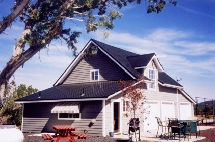 Classic misty grey siding is beautifully contrasted here with a black steel sheet roof from Metal Roof Outlet, Ontario.