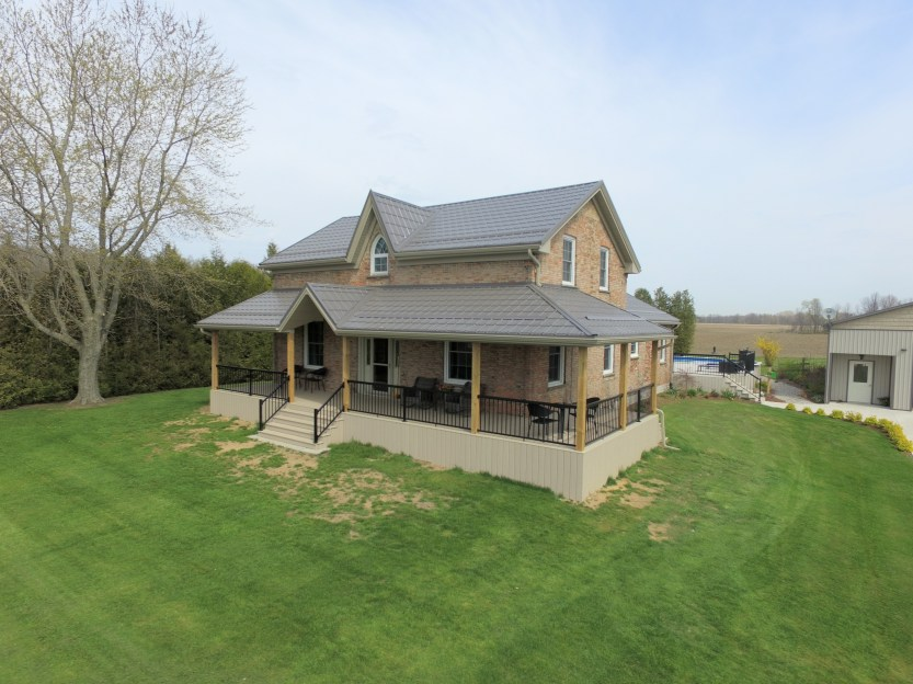 This two story Ontario home with peachy brick has a Metal Slate roof in the colour Charcoal by Metal Roof Outlet.