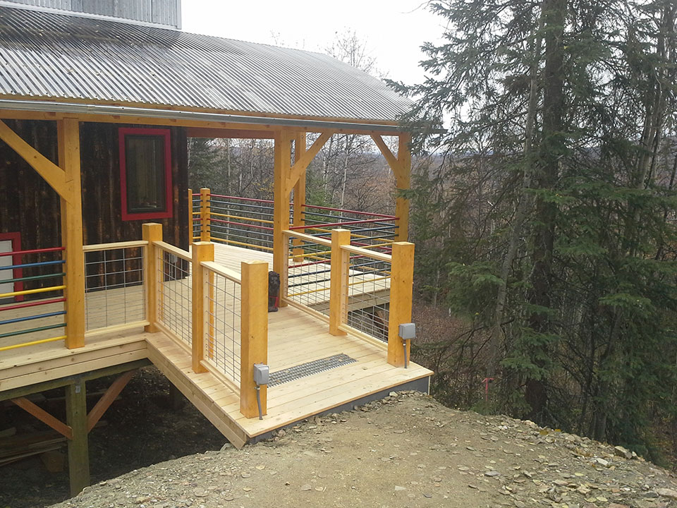 Entry, yellow cedar deck, hog panel and well pipe railing