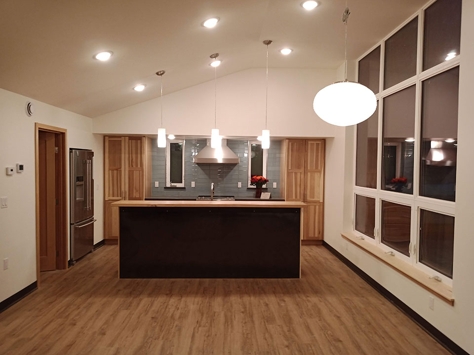 Hickory cabinets and bar top, hot rolled steel below bar, glass tile above stove
