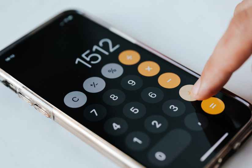 crop anonymous accountant using calculator app on smartphone