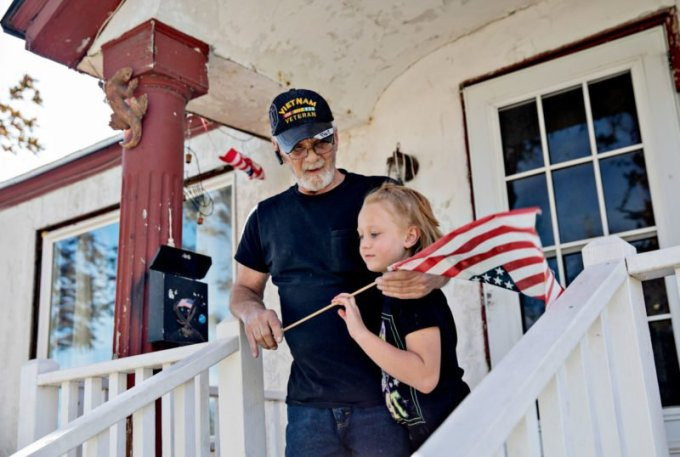 Darrell Reese, a Vietnam veteran, with his granddaughter on his porch. Reese was arrested after he missed a court hearing because, he said, he couldn't afford to put gas in his car. (Kim Raff for ProPublica)
