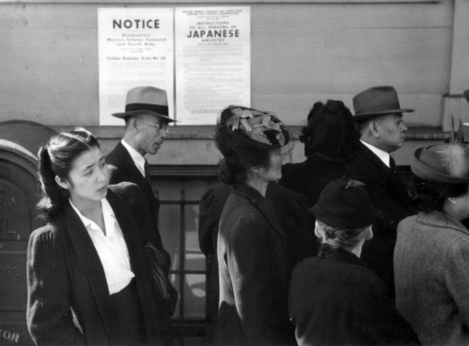 Japanese Americans stand in front of posters with internment orders during World War II. In the 1940s, confidentiality rules were suspended for census records, which facilitated the internment campaign. CREDIT: National Archives