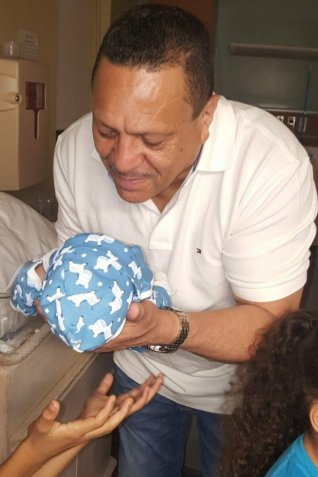 Juan Leonardo Torres in 2016 with his newborn son, Dylan, at the same hospital where he would later seek COVID-19 care. (Courtesy of the Torres family)