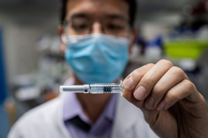 An engineer holds an experimental vaccine for COVID-19 at Sinovac Biotech in Beijing. The Chinese company's vaccine has advanced to human trials. (Nicolas Asfouri/AFP via Getty Images)