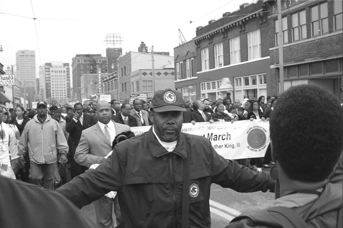 A staff member of the Community Relations Service mediating at a march in Memphis in 2009. His jacket and hat displayed the Department of Justice seal. (Community Relations Service)