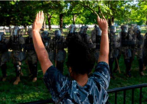 A protester raises her hands near a line of National Guard soldiers deployed near the White House on June 1, 2020. (Photo: Roberto Schmidt)