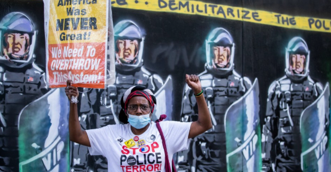 """A protester wearing a mask holds a sign that reads, """"American was never great! We need to Overthrow this system!"""" in front of a mural with New York Police Department officers in full riot gear and the banner above them that says, """"Demilitarize The Police"""" during a march in Manhattan on July 18, 2020. (Photo: Ira L. Black/Corbis via Getty Images)"""