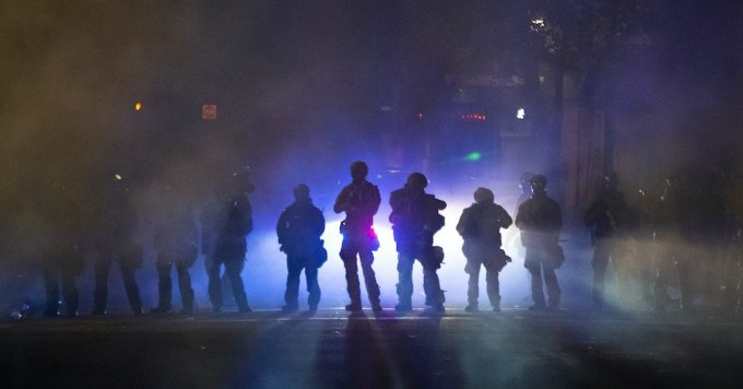 Federal officers walk through tear gas while dispersing a crowd of about a thousand people during a protest on July 21, 2020 in Portland, Oregon. (Photo: Nathan Howard/Getty Images)