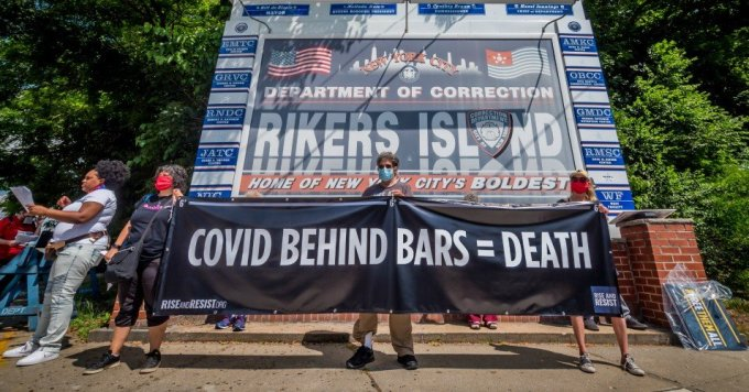 Protesters hold a banner reading COVID BEHIND BARS = DEATH at a rally on Rikers Island in New York City on June 19, 2020. (Photo: Erik McGregor/LightRocket via Getty Images)