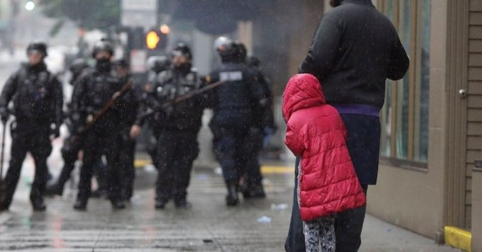 A girl holds on to an adult as police in riot gear stand nearby following protests against the death of George Floyd, a black man who died May 25 in the custody of Minneapolis Police, turned destructive in Seattle, Washington on May 30, 2020. (Photo: Jason Redmond/AFP via Getty Images)