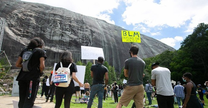Black Lives Matter protesters gather in front of the Confederate carving in Stone Mountain Park on June 16, 2020 in Stone Mountain, Georgia. The march is to protest confederate monuments and recent police shootings. Stone Mountain Park features a Confederate Memorial carving depicting Stonewall Jackson and Robert E. Lee, President Jefferson Davis. (Photo by Jessica McGowan)