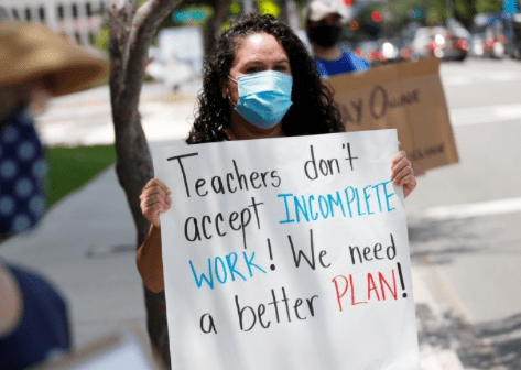 First grade teacher Yolanda Vasquez stands in protest along with other teachers and counselors in front of the Hillsborough County Schools District Office on July 16, 2020 in Tampa, Florida. (Screenshot from Photo: Octavio Jones/Getty Images)
