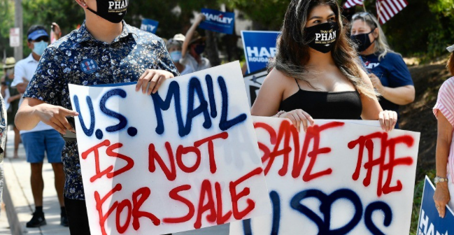 Sergio Escobar, and his sister, Mariana Escobar, join about 100 other protesters during a Harley Rouda rally against changes to the United States Postal Service in Newport Beach, California, on August 18, 2020. The event was organized by Indivisible OC. (Photo: Jeff Gritchen/MediaNews Group/Orange County Register)