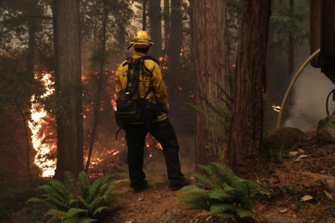 A Cal Fire firefighter keeps an eye on a blaze in front of a home near Boulder Creek, California, on Aug. 19. (Nhat V. Meyer/MediaNews Group/The Mercury News)