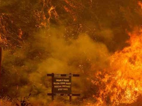 A sign warning people about Covid-19 is surrounded by flames during the Hennessey fire near Lake Berryessa in Napa, California on August 18, 2020. The Hennessey fire has merged with at least 7 fires and is now called the LNU Lightning Complex fires. Dozens of fires are burning out of control throughout Northern California as fire resources are spread thin. (Photo: by Josh Edelson/AFP via Getty Images)