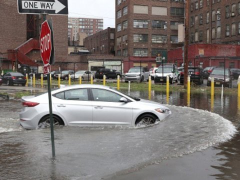 A car drives through a flooded intersecton as Tropical Storm Fay passes through the New York City area on July 10, 2020 in Hoboken, New Jersey. (Photo: Gary Hershorn/Getty Images)