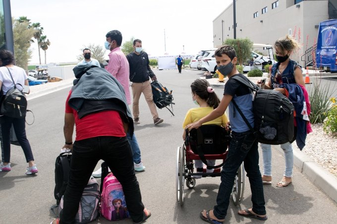 A family from Brazil, seeking asylum in the U.S., prepares to board a chartered bus that will take them from Somerton to the Casa Alitas shelter in Tucson. This family was fortunate: Men and women routinely are separated during processing at the border. (Photo by Kamilah Williams/Cronkite Borderlands Project)