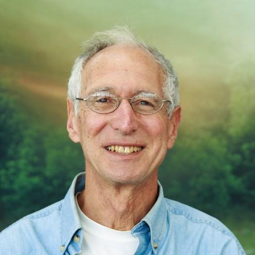 Professor Bluestein stands before a natural backrop