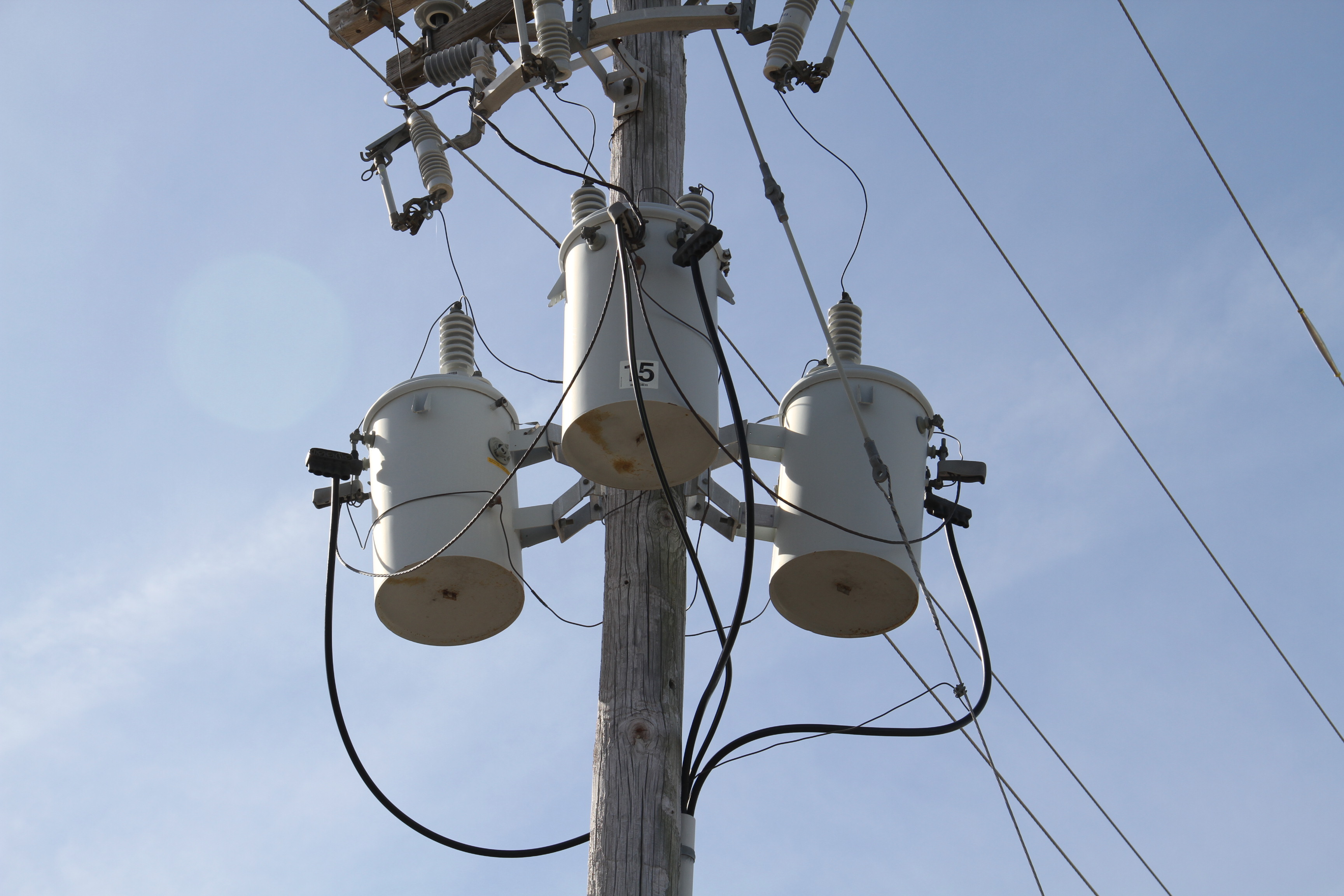 Three Phase Transformers On Pole With Light Blue Sky