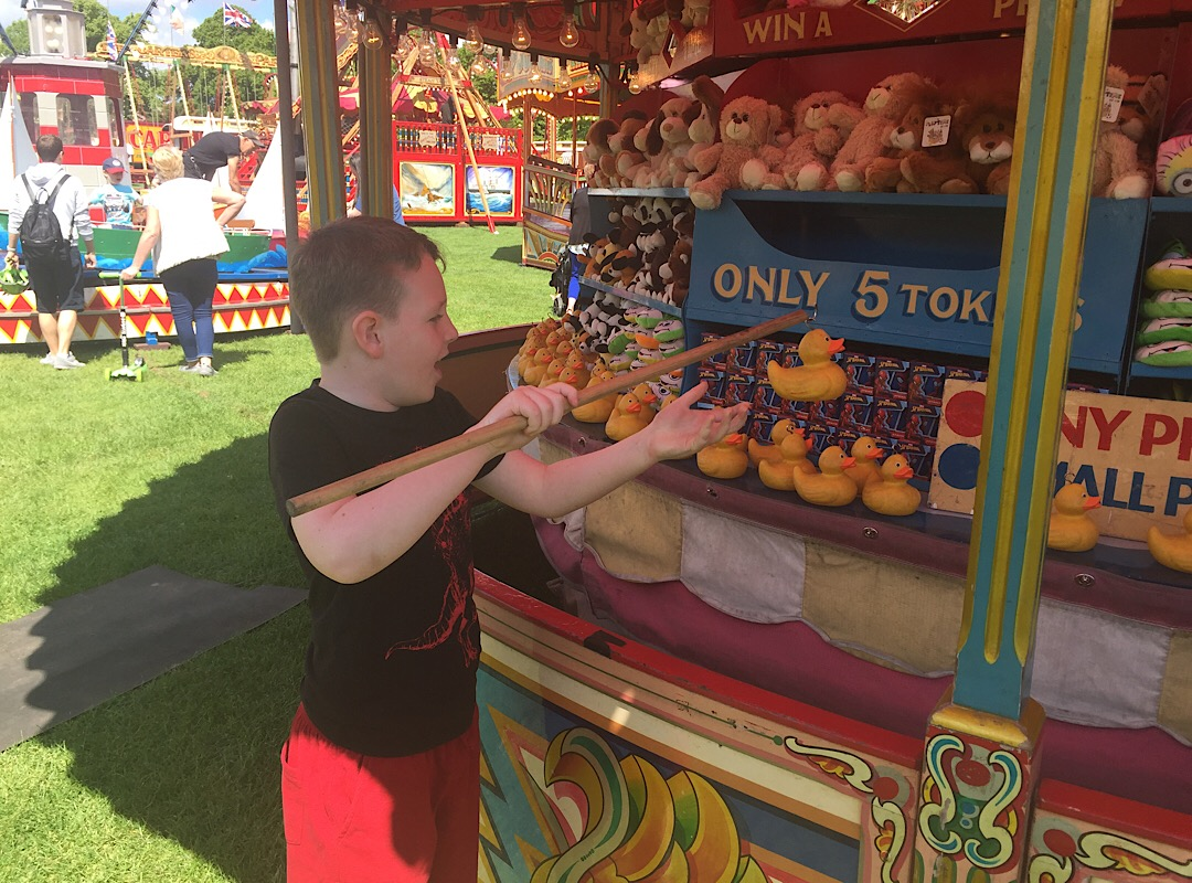 Boy Child hooking a duck at Carters steam fair