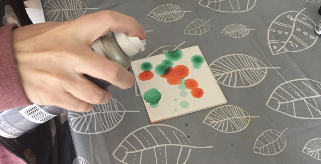 Using compressed air to spread the alcohol ink on the tile