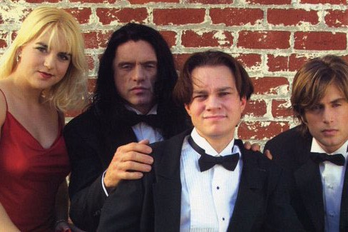 the room cast in tuxedos and a red dress