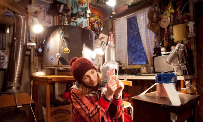 jodie whittaker sitting in a shed full of retro toys in the adult life skills film