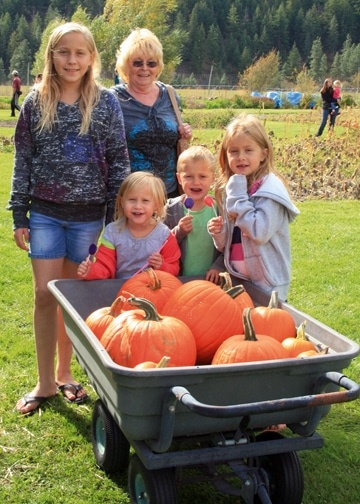 Shan Chute and her grandchildren, Talia (left, rear) and twins Hadley and Hudson and their sister Larkin Freel (front, left to right) made the trip from Brewster and scored a wagonload of luscious orange globes for pie and jack-o'-lanterns.