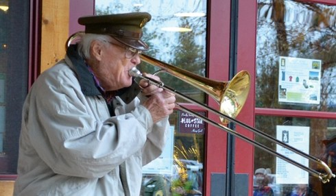 """Royal Canadian Air Force Sergeant Frank Mally served in the Army's 25th evacuation hospital in the Solomon Islands. He played """"Taps"""" and """"Amazing Grace"""" for those gathered at the Mazama Store. Photo by Laurelle Walsh"""