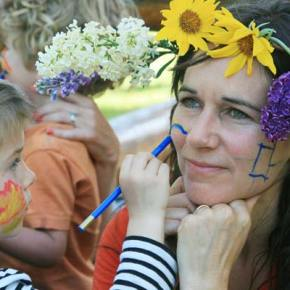 Face Time. Ally Hovee, 3, makes sure her mother, Melissa Raye, is suitably festooned for the Mayfair celebration organized in the Twisp park last week by Sarah Fox of Wildflowers Preschool and Tania Gonzalez Ortega of Rainbow Bridge Day Care. Photo by Marcy Stamper