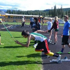 Jaymis Hanson warming up on starting blocks with other LBHS track team members preparing for their events. Photo by Laurelle Walsh