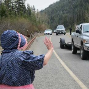 Georgia Sanders waves to motorists passing through the Silver Star   gate while Sheri's Sweet Shoppe owner Doug Mohre, in background, hands   out candy. Photo by Don Nelson