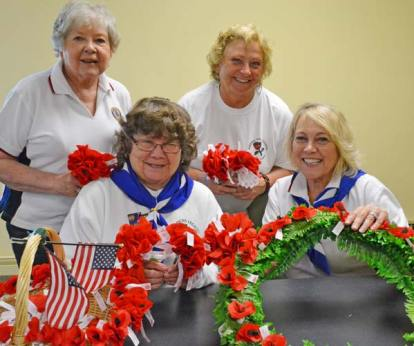 American Legion Auxiliary members Janet Glassburn, left, Lois McLean, Susie Gardner and Gail Surette prepare poppies and a wreath to honor veterans on Memorial Day.  Photo by Laurelle Walsh