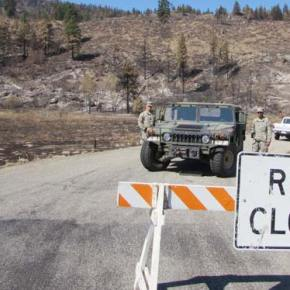"Standing Guard. Corporal Harris, left, and Private Henhert of the National Guard checked IDs this week on Gold Creek Loop Road, part of the Guard's program of ""wellness checks"" on homes throughout the fire area to provide information and assistance. Only residents and other authorized persons were being allowed to proceed up Gold Creek. Photo by Joanna Bastian"