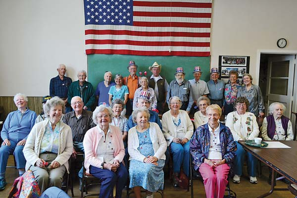 "Four score or more .  The dining room at the Methow Valley Senior Center was packed on Friday to celebrate the annual Over 80 Party. Gentlemen 80 years old and better wore Uncle Sam-style top hats; ladies were draped with silver, red and blue beads; and anyone who had reached their ninth decade dined for free. After a round of ""Happy Birthday,"" some red, white and blue cupcakes and a little spirited bubble blowing, the celebrants assembled for a group portrait to document the day. Photo by Laurelle Walsh"