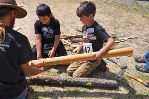 Eric Wittenbach helps Pascal Sherman and Methow Valley Elementary students peel poles for the pit house. Photo by Ray Leaver