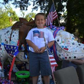 "Six-year-old Max Bennett celebrates the Fourth of July in Twisp on a parade float with ""poppa's pig,"" owned by his grandfather, Bob Ulrich. Bennett had been in the parade ""lots of times"" before, he said. Photo by Laurelle Walsh"