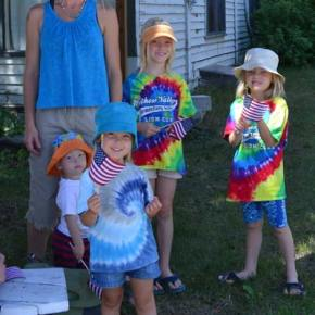 Lindsay Frady and kids watch the parade from a shady yard. Photo by Laurelle Walsh