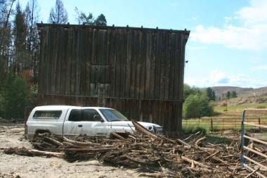 Kim and Lenore Maltais surmise that their pick-up truck, which was swept to a new spot by the surging creek, protected their barn from the flood. Photo by Marcy Stamper, Methow Valley News