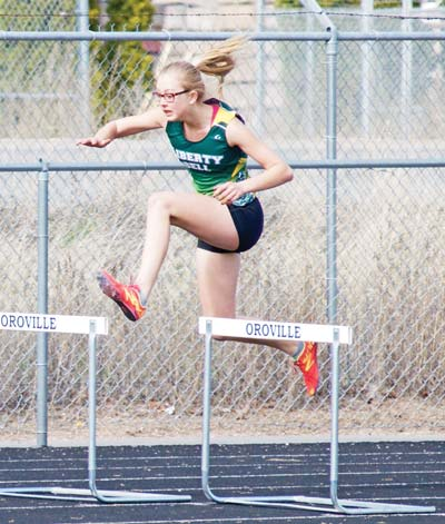Photo courtesy of Erik Brooks Athena Milani on her way to victory in the 300-meter hurdles.