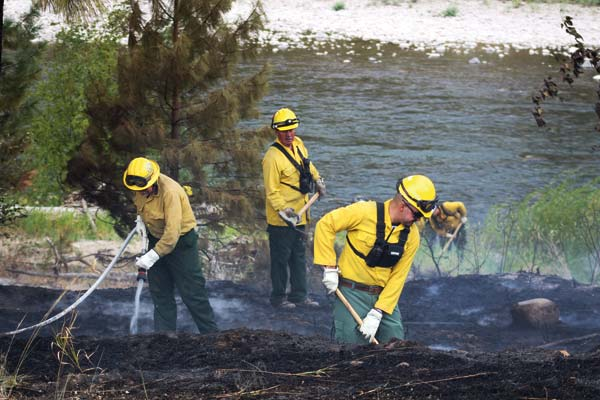 Photo by Don Nelson Okanogan County Fire District 6 firefighters mopped up after controlling a brush fire south of Carlton last Thursday.