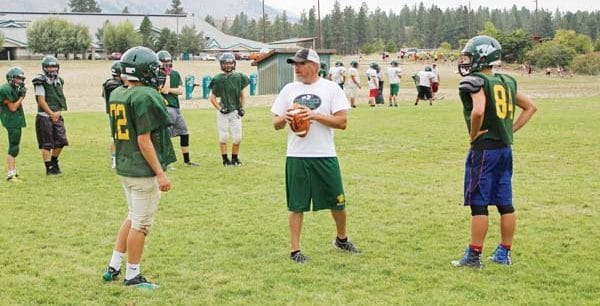 Photo by Don Nelson Head coach Steve White, center, talks about passing with two Mountain Lion players at practice this week. Liberty Bell hosts Brewster on Friday in its opening game of the season.