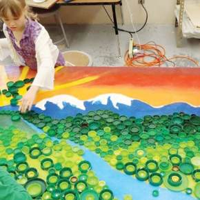 Home school students make a colorful mural out of bottle caps