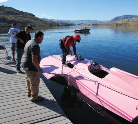 Photo by Joanna Bastian Dale Burnison climbs aboard Country Girl for the initial test run of his newest 7-liter hydroplane. Crewmates hold the boat steady, while a chase boat waits in the calm morning waters of Lake Pateros.
