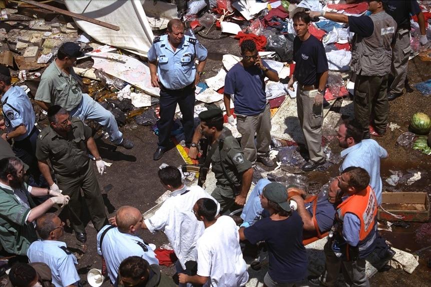 """إخلاء المصابين بعد العملية الثلاثية في""""محانيه يهودا""""، المصدر: الأرشيف الحكومي الإسرائيلي."""